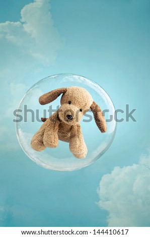 Childhood dreaming. Cute puppy toy floating in a soap bubble in the sky