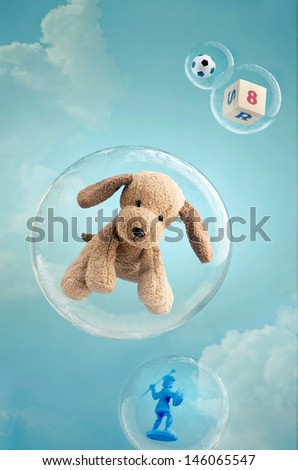 Childhood dreaming. Toys floating in soap bubbles in the sky