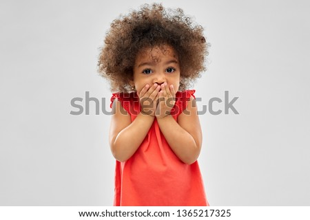 childhood, expression and emotion concept - confused little african american girl covering mouth by hands over grey background Foto stock ©