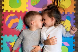 childhood, family friendship, games - close up portrait Two funny joy happy smiling little toddler peschool kids siblings twins brother with sister have fun lie playing on puzzles mat at home indoors