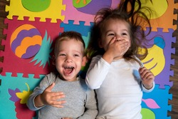 childhood, family friendship, games - close up portrait Two funny joy happy smiling little toddler peschool kids siblings twins brother with sister have fun lie laughing on puzzles mat at home indoors