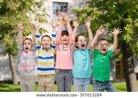 childhood, fashion, gesture and people concept - happy smiling friends raising fists and celebrating victory over summer campus background #397613284