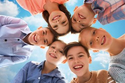childhood, fashion, summer, friendship and people concept - happy smiling children faces over blue sky and clouds background