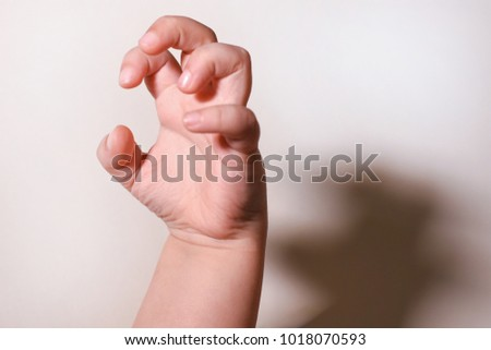 Childhood fears. Gesture with a child's hand with a shadow symbolizes the child's fear #1018070593