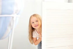 childhood, fun and people concept - happy smiling beautiful little girl hiding behind room door. The child plays hide and seek at home. Positive baby. girl is peeking from behind door and is surprised