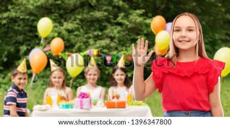 childhood, greeting and people concept - beautiful smiling girl in red shirt and skirt waving hand at birthday party over friends in summer park background #1396347800