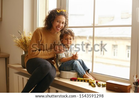 Childhood, happiness, joy and family concept. Indoor shot of joyful young mixed race woman sitting on windowsill with her two year old son who is wearing round eyeglasses. Mother playing with baby