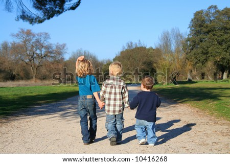 stock photo : Childhood happiness. Three Kids Holding Hands in a nature reserve