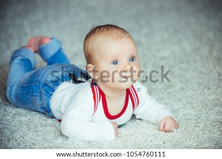 Childhood, infancy, newborn. Infant crawl on floor carpet. Child development concept. Baby with blue eyes on adorable face. Innocence, beauty, purity. #1054760111