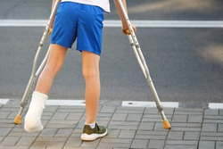 Childhood injuries. Young boy in orthopedic cast on crutches walking on the street near the road. Child with broken leg on crutches, ankle injury. Bone fracture and ankle fracture