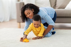 childhood, kids and people concept - happy african american mother and her baby son playing with toy car together on sofa at home