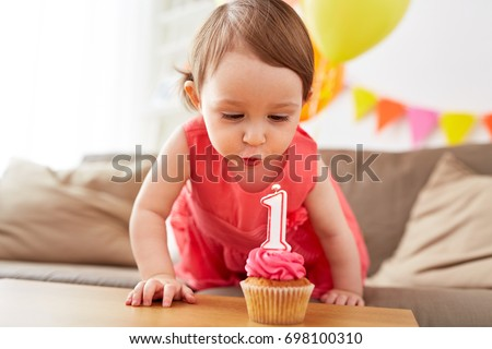 childhood, people and celebration concept - happy baby girl blowing to candle with number 1 on cupcake on birthday party at home