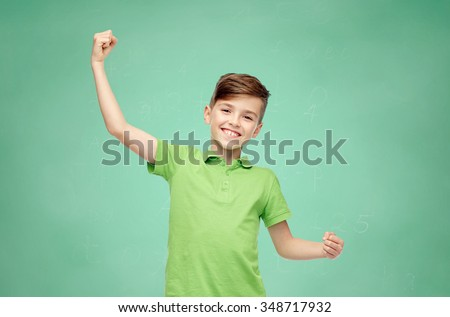 childhood, power, strength and people concept - happy smiling boy in green polo t-shirt showing strong fists over green school chalk board background