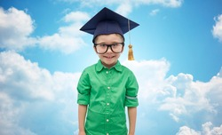 childhood, school, education, learning and people concept - happy boy in bachelor hat or mortarboard over blue sky and clouds background