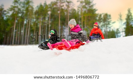 childhood, sledging and season concept - group of happy little kids sliding on sleds down snow hill in winter over forest background Stockfoto ©