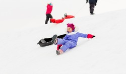 childhood, sledging and season concept - group of happy little kids with sleds on snow hill in winter
