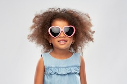 childhood, summer accessory and valentines day concept - happy little african american girl in heart shaped sunglasses over grey background