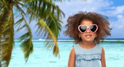 childhood, summer accessory and valentines day concept - happy little african american girl in heart shaped sunglasses over tropical beach background in french polynesia