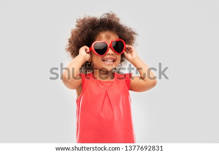 childhood, valentine's day and summer concept - happy little african american girl in heart shaped sunglasses over grey background #1377692831