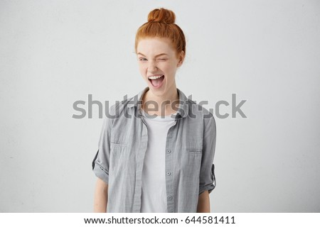 Childish and playful red haired teenage girl winking at camera, keeping mouth wide opened standing against blank studio wall background with copy space for your text or promotional information