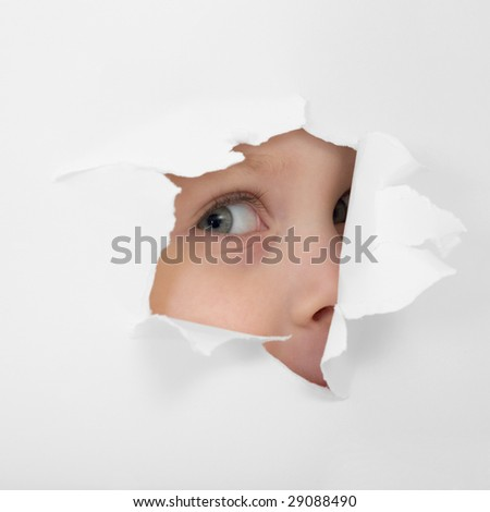 Childish eye looking from hole in white paper