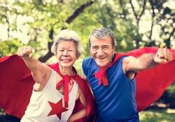 Childlike seniors wearing superhero costumes
