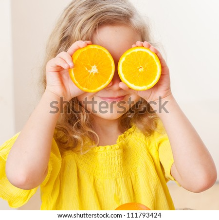 Childr with oranges. Happy little girl with fruit at home.