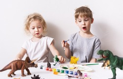 Children a boy and a girl are passionate and paint with figures and brush figures of toy dinosaurs.