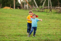 children - a boy in a blue T-shirt and a girl in yellow play a foam plastic toy red plane in nature