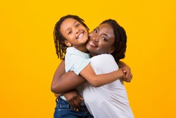 Children Adoption Concept. African American Mother Hugging Her Foster Child, Yellow Studio Background. Copy space
