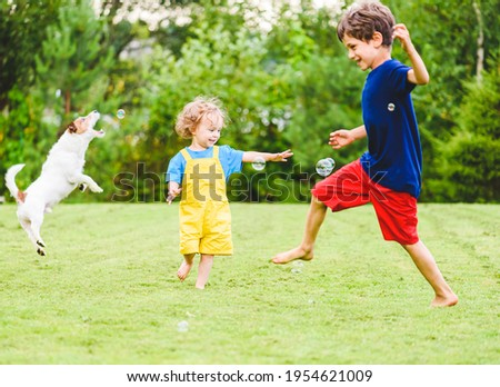 Children and family pet dog playing with funny soap bubbles on hot sunny summer day at backyard lawn Foto stock ©