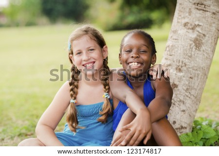Children and friendship, portrait of two young girls hugging, smiling and looking at camera while sitting near tree in park