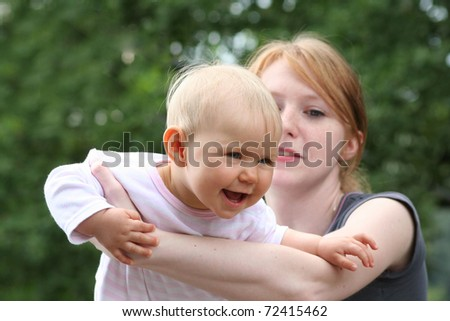 children and mother playing outdoors - stock photo