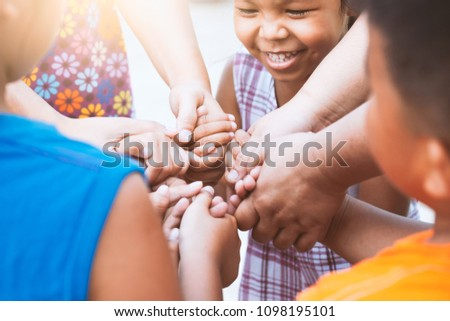 Children and parent holding hands and playing together with unity and teamwork #1098195101