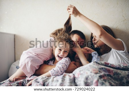 Children and parents rest in the morning in bed. They indulge, hug. Twins. Three daughters.