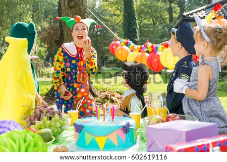 Children and party entertainer wearing funny costumes during birthday