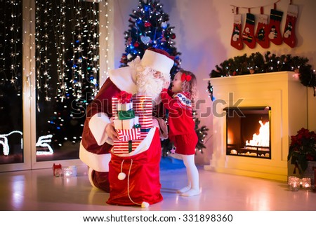 Stock Photo Children and Santa Claus at fireplace on Christmas eve. Family celebrating Xmas. Decorated living room with tree, gifts, fire place, candles. Winter evening at home for parents and kids.