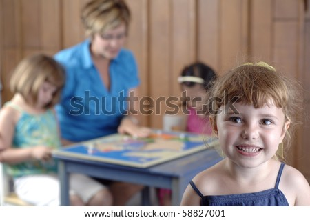 Children and teacher play and learn geography by using a puzzle map. - stock photo
