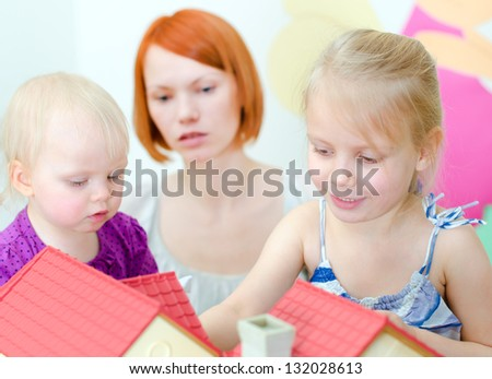Children and their mother playing with dollhouse