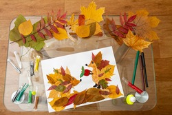 Children applique from dry leaves on the autumn theme. Hedgehogs and apple