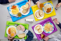 Children are having lunch in the school cafeteria. Top view of dishes on colored trays.