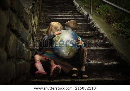 Children are holding the planet earth on wet dark stairs for a weather or season concept about the environment. Elements of this image furnished by NASA.