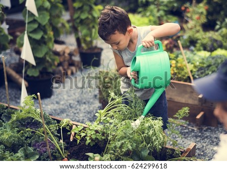 Children are in the garden watering the plants
