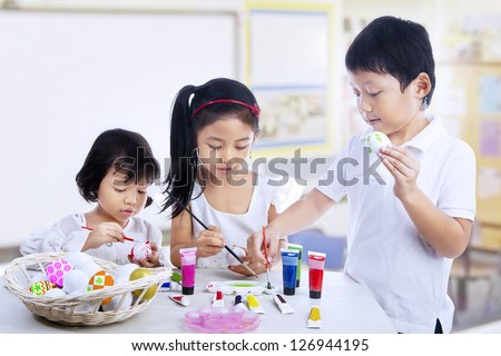 Children are painting easter eggs in art class
