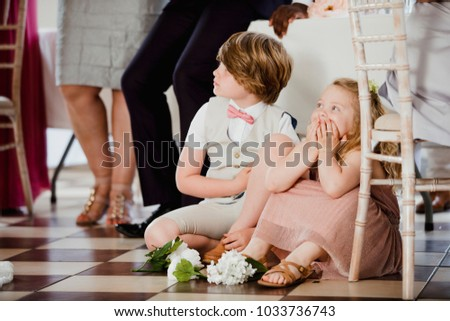 Stock Photo Children are sitting on the dancefloor by a table at a wedding. They are watching the bride and groom share their first dance.