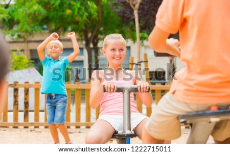Stock Photo Children are teetering on the swing on the playground.