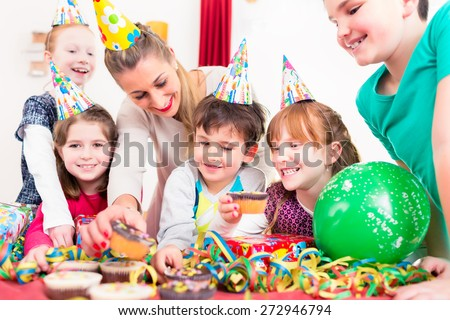 Children at birthday party grabbing muffins and cake, the kids are wearing hats, balloons and paper streamers for decoration