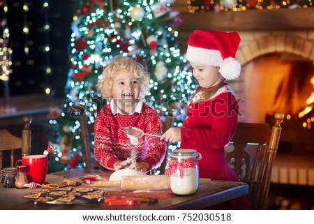 Children baking Christmas cookies at fire place and decorated tree. Kids bake Xmas sweets. Family with kids celebrating Christmas at home. Boy and girl cooking in the kitchen. Winter fun for children