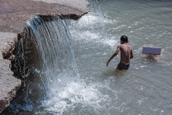 Children bathe in the flowing dirty water of the river. Unsanitary conditions.
