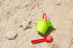Children beach toys buckets, spade, shovel on sand. Sunny day on the seaside. Star and shell form. Kids summer activity